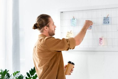 handsome man in shirt putting on card at white board and holding paper cup in office