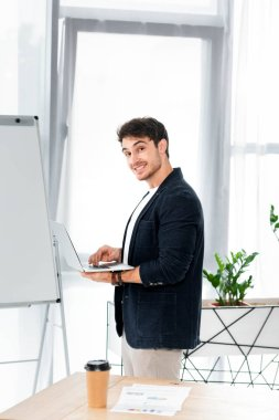 Handsome and smiling man in shirt holding laptop and looking at camera in office stock vector
