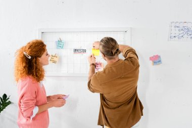 attractive businesswoman in pink sweater looking at her friend putting card on white board