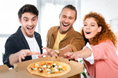 selective focus of three smiling friends taking pizza from box
