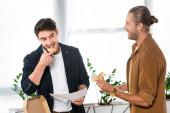 Fotografia due amici sorridenti mangiare pizza e tenendo la carta in ufficio