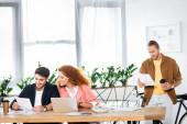 tři usmívající se přátelé dělají papírování a sedí u stolu v kanceláři