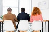hátnézetben három barát ül székek hivatalban