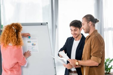 friends doing paperwork and woman putting document on flipchart in office