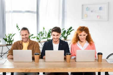 three smiling friends sitting at table and using laptops in office