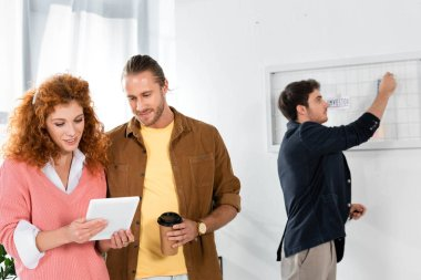 friends looking at digital tablet and man putting card on white board