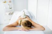 žena ležící na masážní rohoži s bylinnými kuličkami na zádech