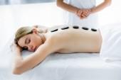 oříznutý pohled na maséra dělá masáž horkými kameny u ženy v lázních