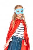 Fotografia ragazzo sorridente in maschera e mantello rosso guardando la fotocamera isolata sul bianco