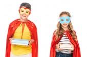 vista frontale di due bambini sorridenti in maschere e mantelli eroe tenendo libri isolati su bianco
