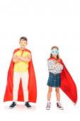 vista a tutta lunghezza di due bambini in mantelli eroe in piedi con le braccia incrociate su bianco
