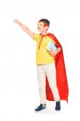 vista a tutta lunghezza del bambino in maschera e mantello eroe tenendo libri isolati sul bianco
