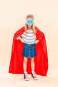 pohled na dítě v plné délce v masce a hrdinově plášti, který stojí s rukama na růžových