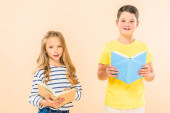 Fotografie front view of  two smiling kids holding books isolated on pink