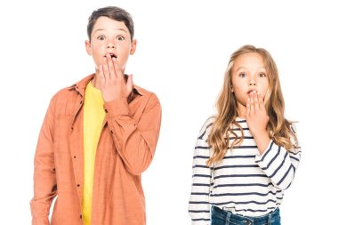 front view of shocked children covering mouths with hands isolated on white