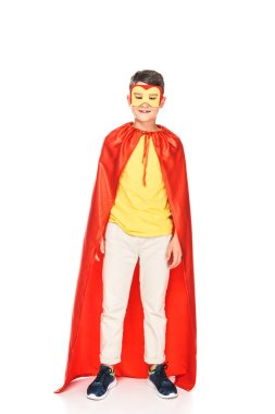 Full length view of smiling kid in mask and hero cloak on white stock vector