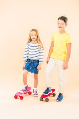full length view of two smiling kids with skateboards on pink