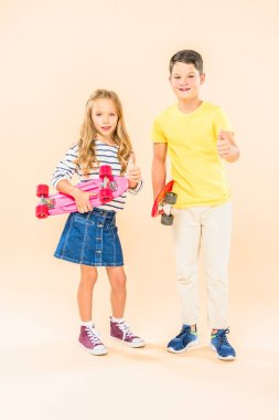 full length view of two smiling kids holding skateboards and showing thumbs up on pink