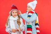 zwei lächelnde Kinder in Winter-Outfits isoliert auf rot