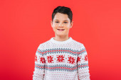 front view of smiling kid in sweater isolated on red