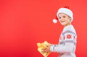 Fotografie lächelnde Kind in santa Hut halten vorhanden isoliert auf rot