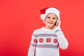 Frontansicht eines lächelnden Kindes mit Weihnachtsmannmütze, das auf dem Smartphone isoliert auf Rot spricht