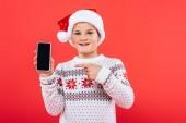 elülső kilátás mosolyogva gyerek Santa hat mutatva ujjal a smartphone üres képernyőn izolált piros