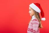 Fotografie Seitenansicht des lächelnden Kindes in Pullover und Santa Hut isoliert auf rot
