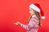 Fotografie boční pohled na usmívající se dítě ve svetru a Santa klobouku s napřaženou rukou izolovanými na červené