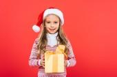 pohled na usmívající se dítě v Santa klobouku, současné izolované na červeném
