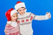 due bambini sorridenti in cappelli santa prendendo selfie isolato sul blu