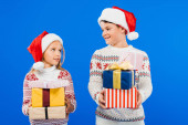 Fotografie dva usmívající se děti v Santa klobouky s dárky, které se na sebe dívají izolovaně na modrém