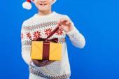 Fotografie oříznutý pohled na chlapce v Santa klobouku a svetru se dárkem izolovaný na modrém