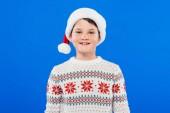 Fotografie Vorderansicht des lächelnden Kindes in Santa-Hut und Pullover isoliert auf blau