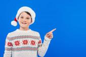Frontansicht eines lächelnden Kindes mit Weihnachtsmütze, das mit dem Finger auf blau zeigt