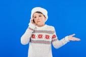 Verwirrtes Kind im Pullover spricht auf Smartphone isoliert auf blauem Grund