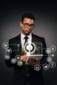 Fotografie african american businessman in glasses using digital tablet on dark background with internet security illustration