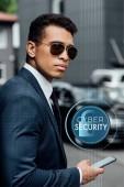 Fotografie pohledný a sebevědomý africký americký podnikatel v obleku a slunečních brýlích pomocí smartphonu s kybernetickou bezpečnostní ilustrací