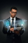 Fotografie african american businessman in glasses using digital tablet on dark background with cyber security illustration