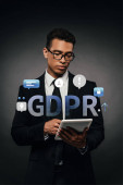 Photo african american businessman in glasses using digital tablet on dark background with gdpr illustration