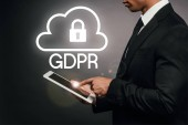 Fotografie partial view of african american businessman using digital tablet on dark background with gdpr illustration