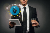 Fotografie částečný pohled na afrického amerického podnikatele držícího kávu jít a digitální tablet na tmavém pozadí s gdpr ilustrací