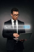 Photo african american businessman using laptop on dark background with search bar illustration