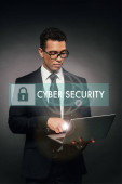 Fotografie african american businessman using laptop on dark background with cyber security illustration