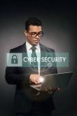 africký americký podnikatel pomocí notebooku na tmavém pozadí s kybernetické bezpečnosti ilustrace