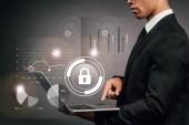 Fotografie částečný pohled na africký americký podnikatel pomocí notebooku na tmavém pozadí s internetové bezpečnostní ilustrace