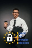 Fotografie happy african american businessman holding newspaper, coffee to go and leather briefcase on dark background with gdpr illustration