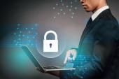 částečný pohled na africký americký podnikatel pomocí notebooku na tmavém pozadí s internetové bezpečnostní ilustrace