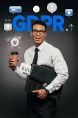 šťastný africký americký podnikatel držící noviny, kávu jít a kožený kufřík na tmavém pozadí s gdpr ilustrací