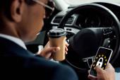 Fotografie Rückansicht eines afrikanisch-amerikanischen Geschäftsmannes mit Smartphone und Kaffeetrinken im Auto mit gdpr-Abbildung